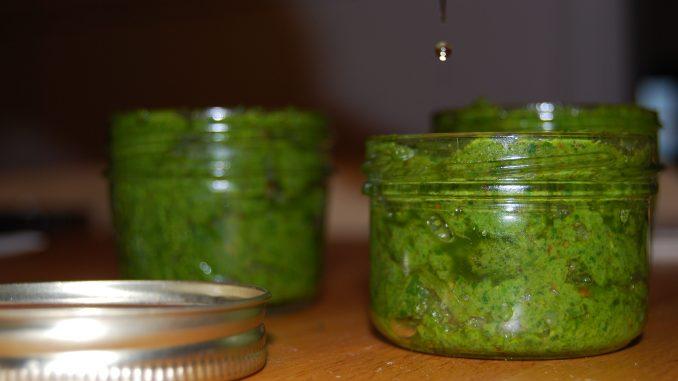 Pots de pesto au basilic avec un filet d'huile qui coule dessus.